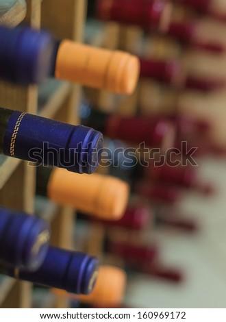 Different wine bottles stacked on wooden racks - stock photo