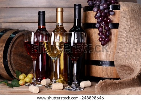 Different wine on table on wooden background - stock photo