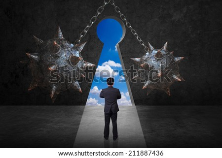 difficult path of businessman front of spike wrecking ball and chain against keyhole on old grunge black wall and bright blue sky background in concept of obstacle and trap on the way of a business  - stock photo