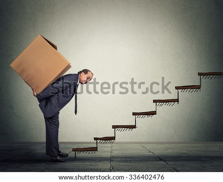 Difficult task challenge concept. Middle aged business man carrying large heavy box on his back upstairs - stock photo