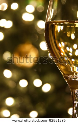 Diffused lights and ornaments from a Christmas tree form the background for a close-up of a glass of white wine. - stock photo
