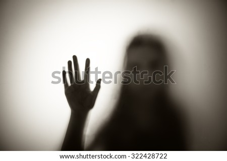 Diffused silhouette of woman through frosted glass