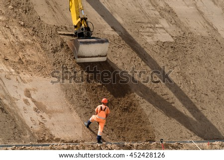 Digger works at new highway construction site - stock photo