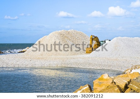 Diggers on the seashore building a breakwater - stock photo
