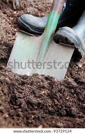 Digging soil with a spade & rubber boots. - stock photo