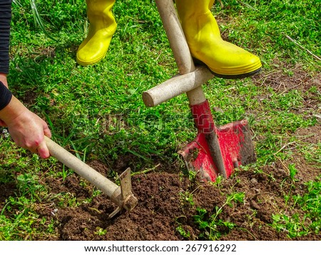 Digging With shovel and hoe in garden - stock photo
