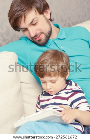 Digital age. Close-up of a small boy using a tablet device spending time together with his father - stock photo