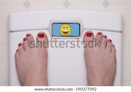 Digital Bathroom Scale Displaying a Happy Emoji - stock photo