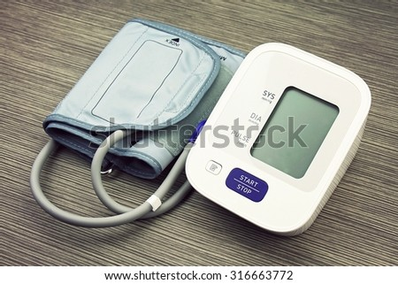 Digital Blood Pressure Monitor on wood background, Medical equipment, Examining equipment. (Vintage Style Color) - stock photo