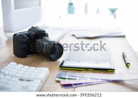 digital camera and colour swatches on an office desk - stock photo