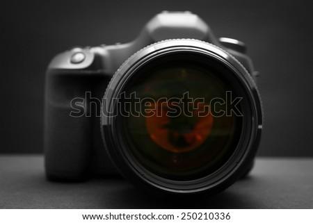 Digital camera on dark background - stock photo