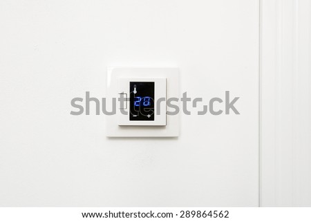 Digital climate control on white wall - stock photo