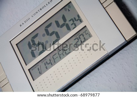 Digital clock against the wall - stock photo