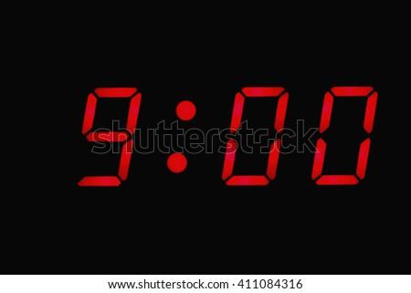 Digital clock closeup displaying 9:00 o'clock - stock photo