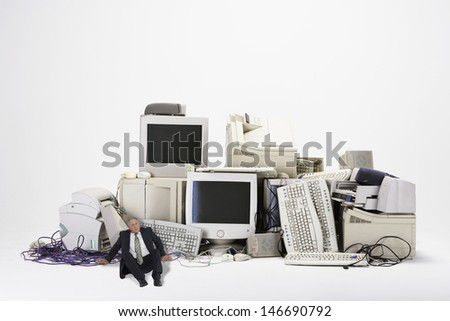 Digital composite of businessman sitting by various obsolete technologies against white background - stock photo