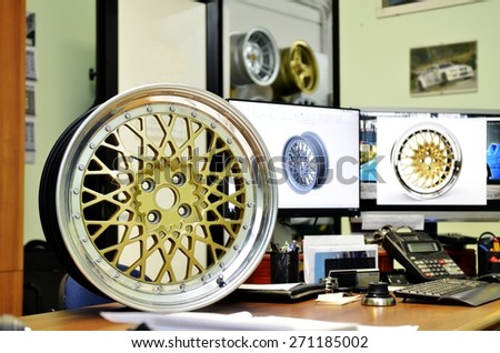 Digital drawing of a homemade circle car realized on a computer next to a specimen real. Rim for cars designed on a computer inside an industrial factory - stock photo