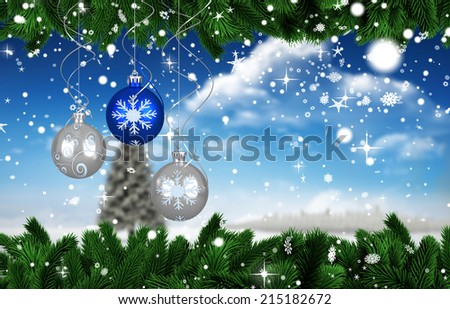Digital hanging christmas bauble decoration against fir tree in snowy landscape