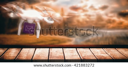 Digital image of a drone holding a cube against country scene - stock photo
