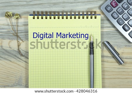 digital marketing writing in notebook. pen and calculator wooden desk. business concept - stock photo