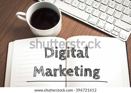 Digital marketing written on notebook , keyboard and coffee on wood table - stock photo