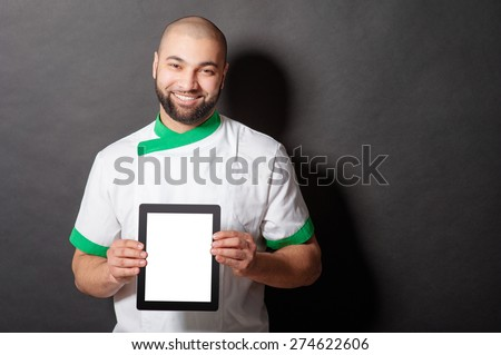 Digital menu. Handsome young arabic chief cook holding tablet computer against blackboard. - stock photo