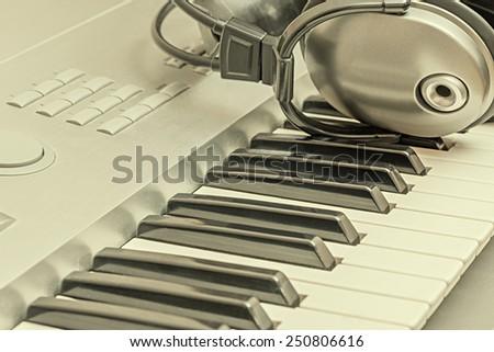 Digital midi keyboard and headphones in the studio.  - stock photo