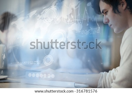 Digital representation of world map against students working on a paper - stock photo