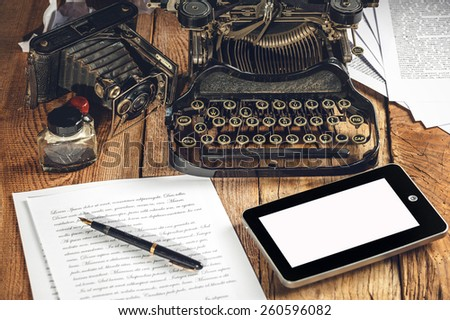 Digital Tablet, analog machine, analog camera when creating a text to an article or study. - stock photo