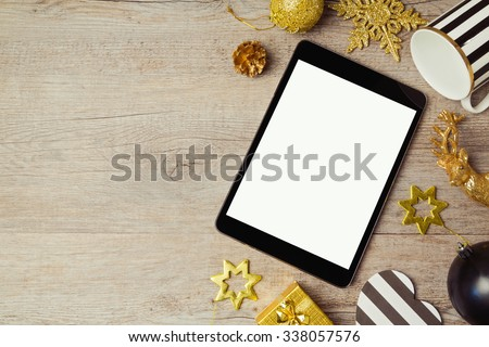 Digital tablet and Christmas golden decorations on wooden background. View from above - stock photo