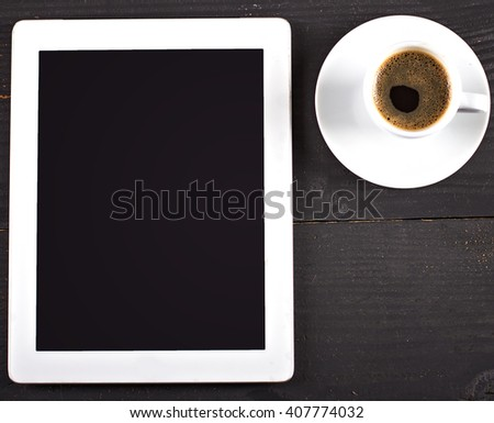 digital tablet and coffee cup on wooden table - stock photo