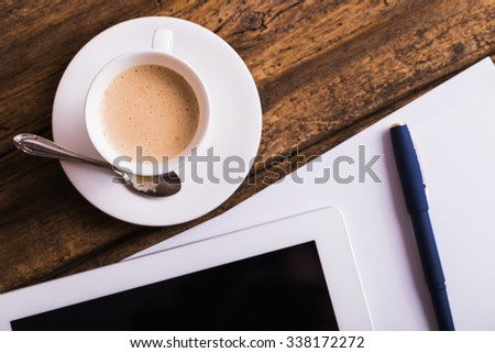 digital tablet and coffee on old wooden background