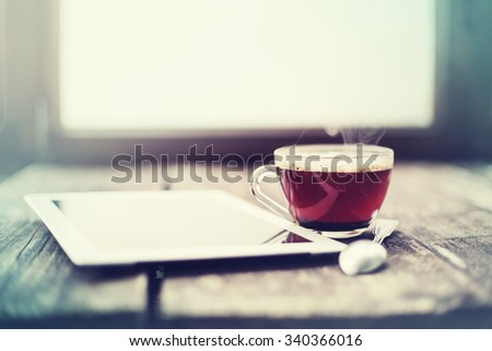 Digital tablet and cup of tea on old wooden desk. Simple workspace or coffee break in morning/ selective focus - stock photo