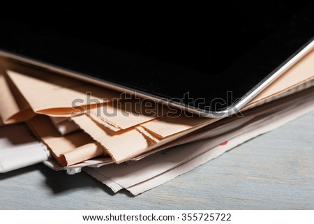 Digital tablet and newspapers  - stock photo