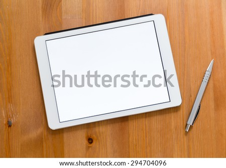 Digital Tablet and pen on a desk and presenting a blank screen for advertising
