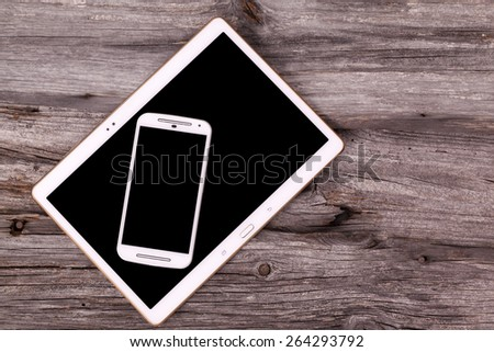 Digital tablet and smart phone on wooden background - stock photo