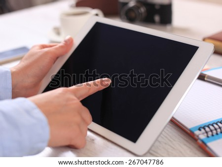 Digital tablet computer with isolated screen in female hands over cafe background - stock photo