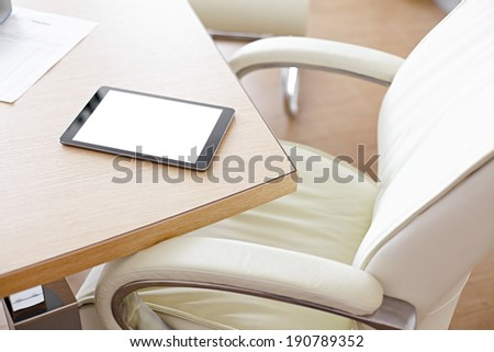 Digital tablet computer with isolated screen on office desk. At office interior. - stock photo