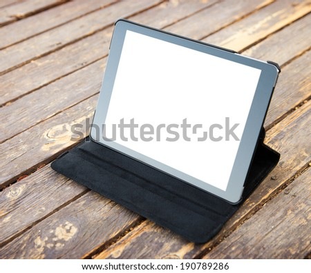 Digital tablet computer with isolated screen on old wood. - stock photo