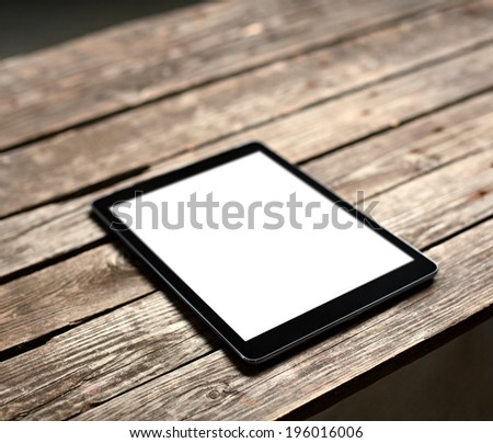 Digital tablet computer with isolated screen on old wooden table - stock photo