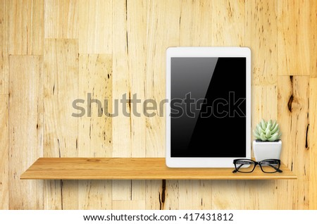 Digital tablet computer with isolated screen with clipping path on bookshelf in the wall. - stock photo