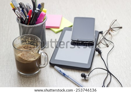 Digital tablet computer with sticky note paper and cup of coffee on wooden desk - stock photo