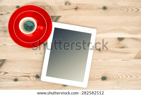 Digital tablet iPad style and red cup of coffee on wooden table. Vintage style toned picture - stock photo