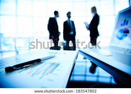 Digital tablet, laptop and financial document with pen at workplace on background of three business partners interacting
