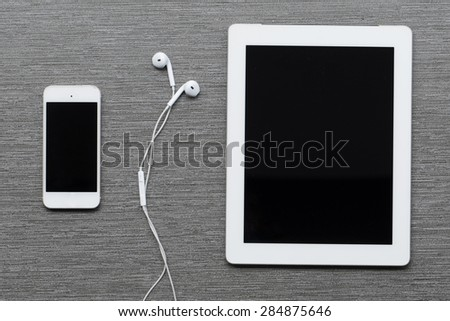 Digital tablet, mobile phone and earphones.  - stock photo