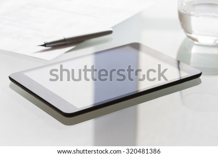 Digital tablet on modern glass table in office - stock photo