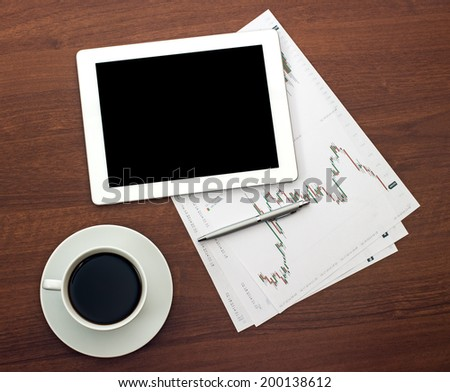 Digital tablet on wooden tablets with documents and pen