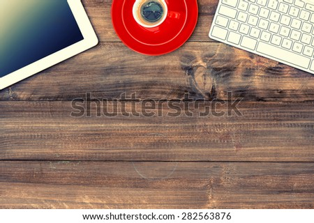 Digital tablet pc, keyboard and red cup of coffee on wooden table. Vintage style toned picture - stock photo