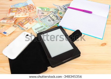 Digital tablet, smart phone and classic notebook with pen on the wood desktop with money (banknotes euro and USA dollars)  in the background. Modern gadgets and retro office accessories with money