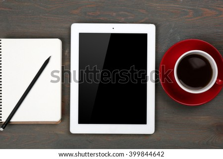 Digital tablet with cup of coffee and notebook on wooden table, closeup