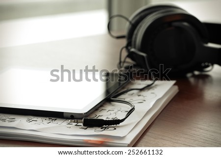 digital tablet with headphones on musical notes papers  with shallow DOF evenly matched and wooden desk - stock photo
